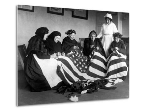 Patriotic Old Female Immigrants Sewing an American Flag under Supervision of Instructor Rose Radin--Metal Print