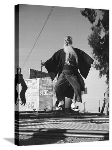 Elderly Japanese Movie Extra Jumping on Trampoline-Ralph Crane-Stretched Canvas Print