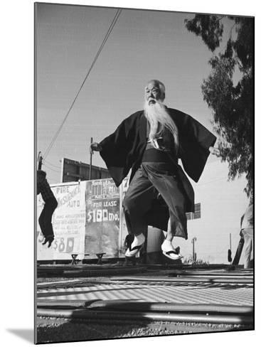 Elderly Japanese Movie Extra Jumping on Trampoline-Ralph Crane-Mounted Photographic Print