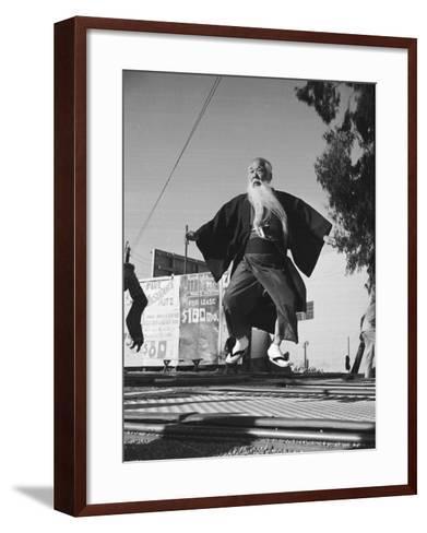 Elderly Japanese Movie Extra Jumping on Trampoline-Ralph Crane-Framed Art Print