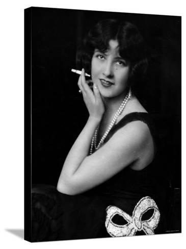 Fashionable Woman with Cigarette Holder in Hand Wearing Long Double Strand Pearl Necklace--Stretched Canvas Print