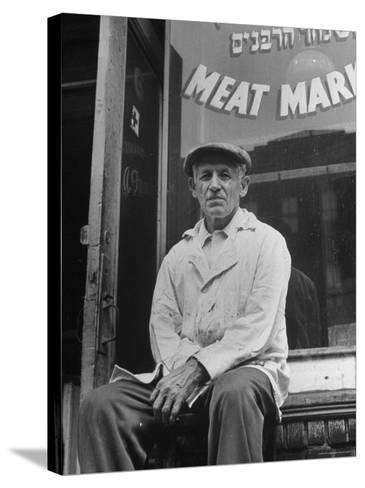 Butcher Taking a Break, Sitting in Front of Meat Market-Ed Clark-Stretched Canvas Print