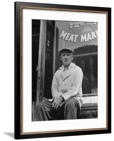 Butcher Taking a Break, Sitting in Front of Meat Market-Ed Clark-Framed Art Print