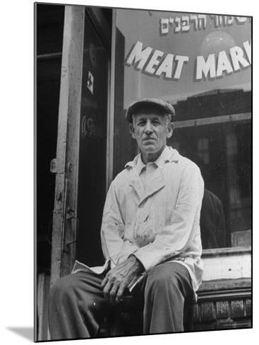 Butcher Taking a Break, Sitting in Front of Meat Market-Ed Clark-Mounted Photographic Print