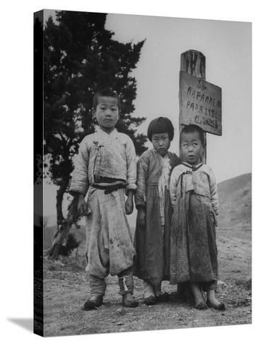 Children Standing in Front of Boundary Zone Sign Written in Russian, English, and Korean-John Florea-Stretched Canvas Print