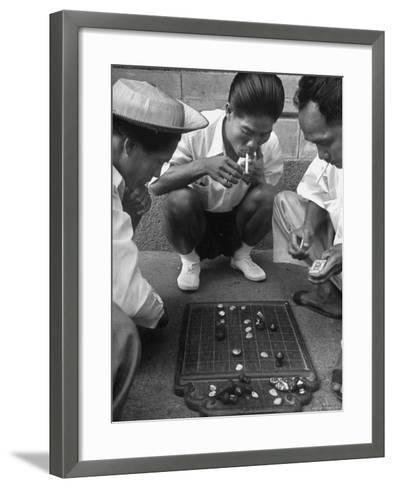 Boys Playing Board Game on Sidewalk in Front of the Trocadero Hotel-Dmitri Kessel-Framed Art Print