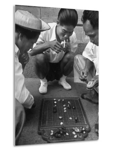 Boys Playing Board Game on Sidewalk in Front of the Trocadero Hotel-Dmitri Kessel-Metal Print