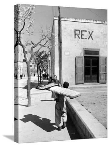 Baker's Apprentice Carrying a Large Tray of Bread Dough-Alfred Eisenstaedt-Stretched Canvas Print