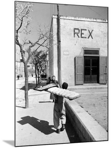 Baker's Apprentice Carrying a Large Tray of Bread Dough-Alfred Eisenstaedt-Mounted Photographic Print