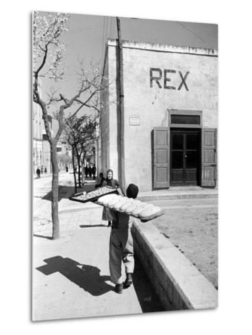 Baker's Apprentice Carrying a Large Tray of Bread Dough-Alfred Eisenstaedt-Metal Print