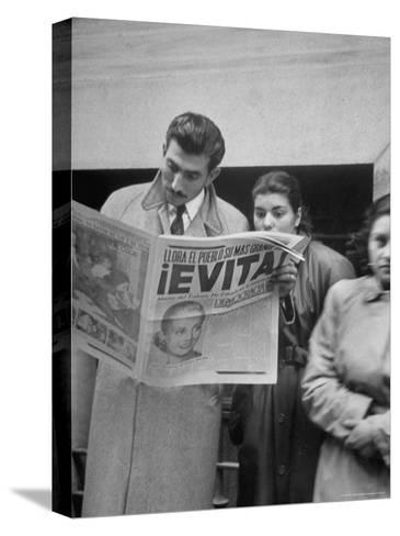 Couple Reading Newspaper Account of the Death of Evita Peron at 33 from Cancer-Alfred Eisenstaedt-Stretched Canvas Print