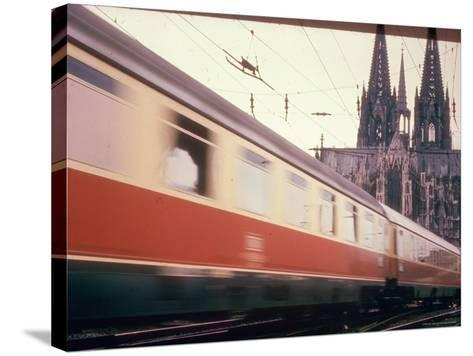 Eurailpass in Europe: Germany's Parsifal Express Speeding Past Cologne Cathedral-Carlo Bavagnoli-Stretched Canvas Print
