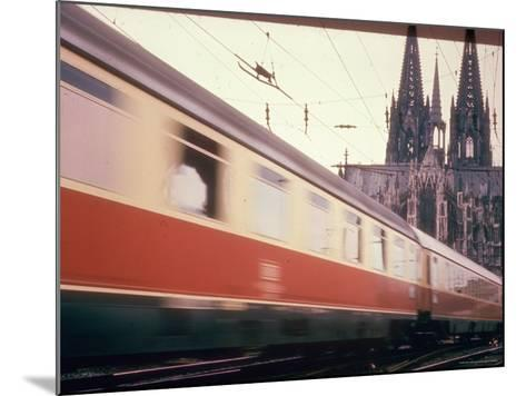 Eurailpass in Europe: Germany's Parsifal Express Speeding Past Cologne Cathedral-Carlo Bavagnoli-Mounted Photographic Print