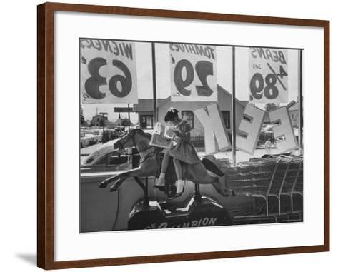 Young Girl Sitting on a Coin Rider Reading a Comic Book at the Supermarket-Dmitri Kessel-Framed Art Print