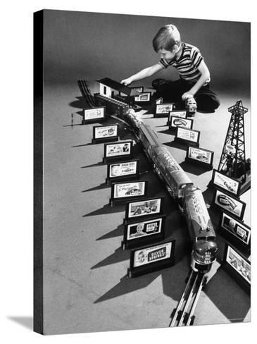 Little Boy Playing with a Toy Train and Billboard Set-Walter Sanders-Stretched Canvas Print