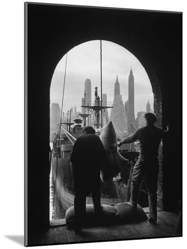 Men Unloading Coffee at Brooklyn Dock. View of Downtown Manhattan in Background-Andreas Feininger-Mounted Photographic Print