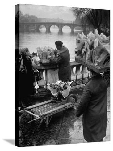Parisian Flower Vendor at Work Stocking His Stall on the Seine with the Pont Neuf in the Background-Ed Clark-Stretched Canvas Print