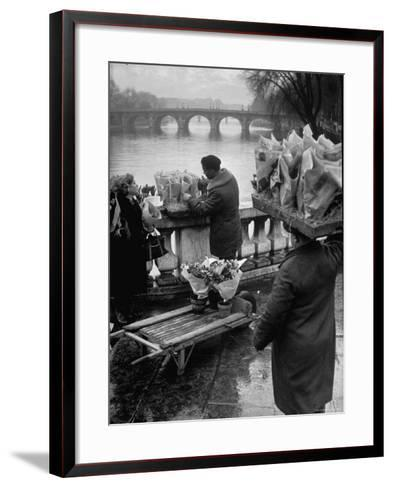 Parisian Flower Vendor at Work Stocking His Stall on the Seine with the Pont Neuf in the Background-Ed Clark-Framed Art Print