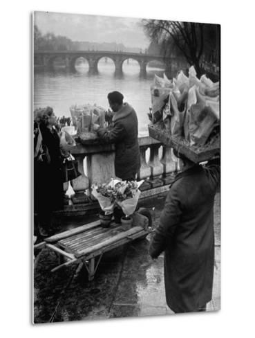 Parisian Flower Vendor at Work Stocking His Stall on the Seine with the Pont Neuf in the Background-Ed Clark-Metal Print