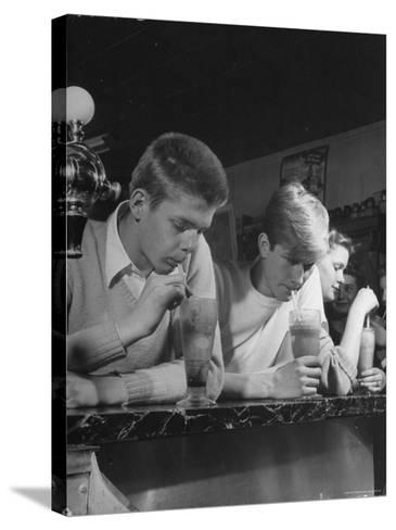 Teen Age Boys and Girls Drinking Milkshakes in Drug Store-Nina Leen-Stretched Canvas Print