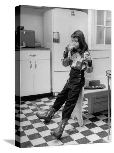 Young Girl Wearing Cowgirl Outfit Drinking Milk and Eating Sandwich in Kitchen-Nina Leen-Stretched Canvas Print