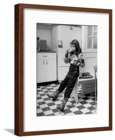 Young Girl Wearing Cowgirl Outfit Drinking Milk and Eating Sandwich in Kitchen-Nina Leen-Framed Art Print