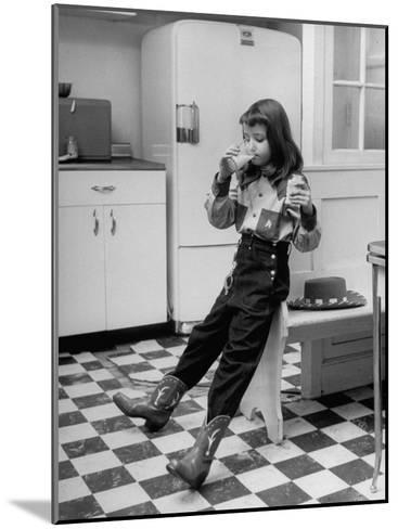 Young Girl Wearing Cowgirl Outfit Drinking Milk and Eating Sandwich in Kitchen-Nina Leen-Mounted Photographic Print