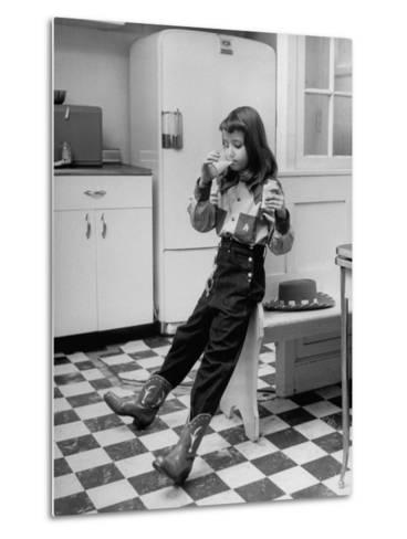 Young Girl Wearing Cowgirl Outfit Drinking Milk and Eating Sandwich in Kitchen-Nina Leen-Metal Print