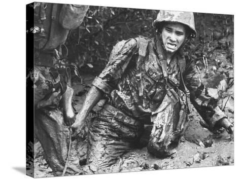 Marine Sinking Into Mud-Larry Burrows-Stretched Canvas Print