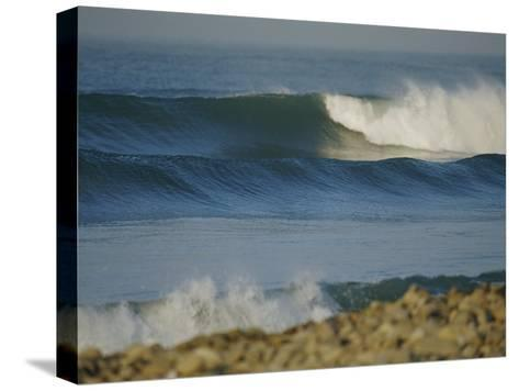 Large Waves Break and Rush to a Rocky Shore at Sunrise-Rich Reid-Stretched Canvas Print