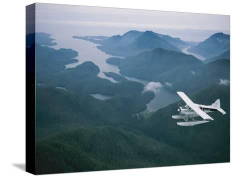 A Beaver Airplane on Floats Flies over Islands and Snowy Mountains-Joel Sartore-Stretched Canvas Print