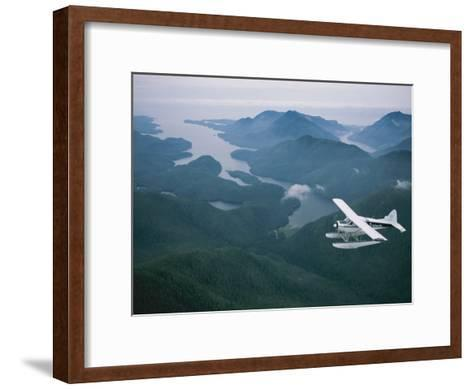 A Beaver Airplane on Floats Flies over Islands and Snowy Mountains-Joel Sartore-Framed Art Print