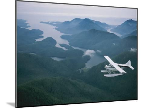 A Beaver Airplane on Floats Flies over Islands and Snowy Mountains-Joel Sartore-Mounted Photographic Print