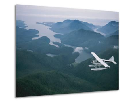 A Beaver Airplane on Floats Flies over Islands and Snowy Mountains-Joel Sartore-Metal Print