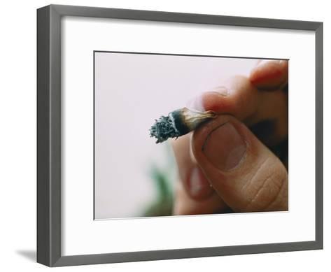 Extreme Close-up of a Marijuana Butt Held Between Two Fingers-Ira Block-Framed Art Print