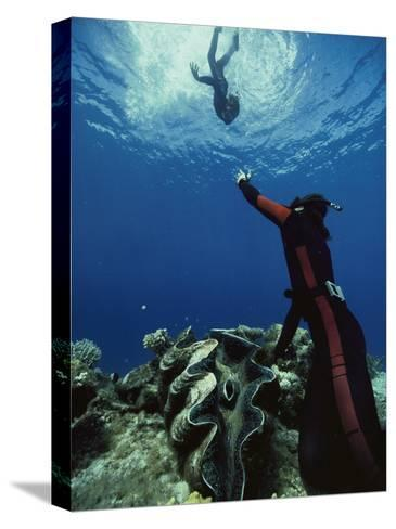 A Diver on the Sea Floor Gestures to Another Diver Who is Descending-Bill Curtsinger-Stretched Canvas Print