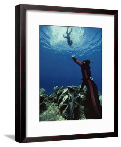 A Diver on the Sea Floor Gestures to Another Diver Who is Descending-Bill Curtsinger-Framed Art Print