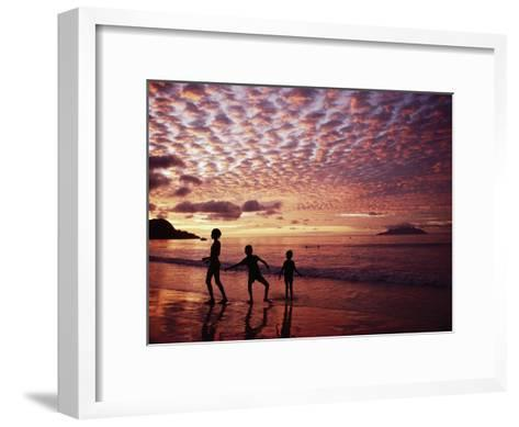 Sunset Reddens a Cloudy Sky as Silhouetted Children Play on the Beach-Steve Raymer-Framed Art Print