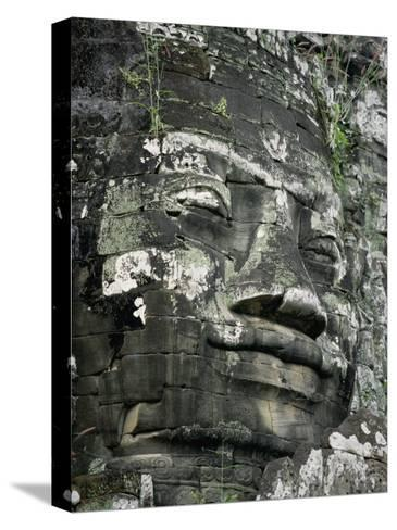 A Serene Likeness of Buddha Sculpted of Stone Peers from a Temple Wall-Paul Chesley-Stretched Canvas Print