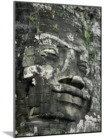 A Serene Likeness of Buddha Sculpted of Stone Peers from a Temple Wall-Paul Chesley-Mounted Photographic Print