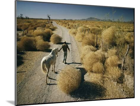 A Man Leads a Horse Down a Dirt Road-Walter Meayers Edwards-Mounted Photographic Print