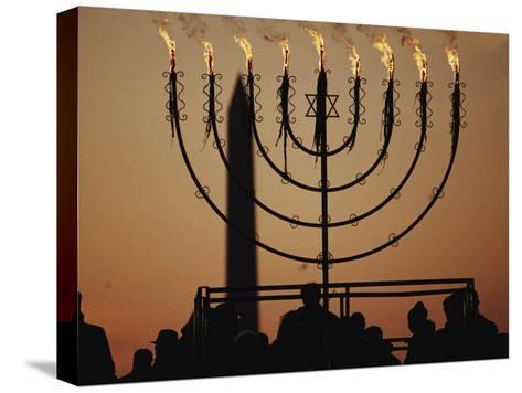 Silhouetted Worshippers Stand Before a Large Menorah Near the Washington Monument-Sam Kittner-Stretched Canvas Print
