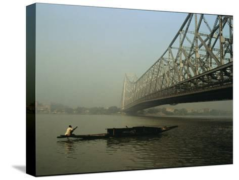 A Man Guides a Boat under a Bridge on the Hooghly River at Calcutta-Ed George-Stretched Canvas Print