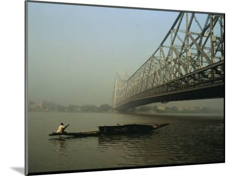 A Man Guides a Boat under a Bridge on the Hooghly River at Calcutta-Ed George-Mounted Photographic Print