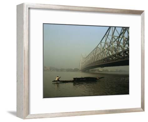 A Man Guides a Boat under a Bridge on the Hooghly River at Calcutta-Ed George-Framed Art Print