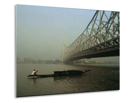 A Man Guides a Boat under a Bridge on the Hooghly River at Calcutta-Ed George-Metal Print