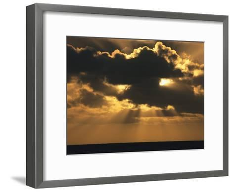 Rays of Sunlight Beam from Behind a Dark Cloud over Water at Twilight-Tim Laman-Framed Art Print