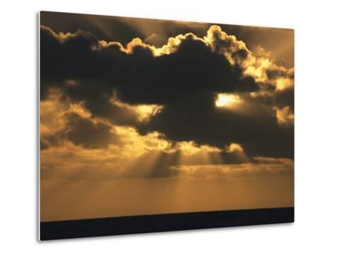 Rays of Sunlight Beam from Behind a Dark Cloud over Water at Twilight-Tim Laman-Metal Print