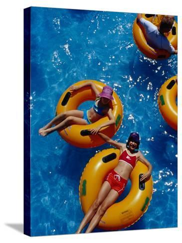 Young Girls Floating in Rubber Rings in Swimming Pool, Gold Coast, Australia-Richard I'Anson-Stretched Canvas Print