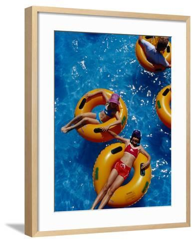 Young Girls Floating in Rubber Rings in Swimming Pool, Gold Coast, Australia-Richard I'Anson-Framed Art Print